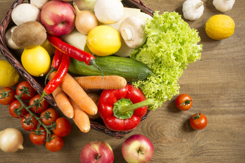 Wicker basket with fruits and vegetables on wooden table royalty free stock photos