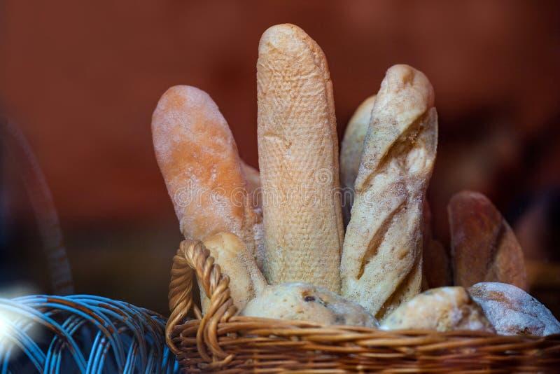 Wicker basket full of baguettes, tasty delicious crusty bread in bakery shopfront. French baguettes in a wicker baske royalty free stock photo