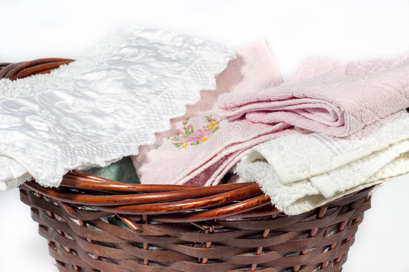 Wicker basket full of hand towels of different colors and patterns. Wicker basket for bathroom containing several hand towels of different colors and patterns stock photo