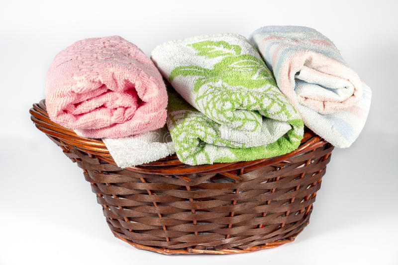 Wicker basket with hand towels of different colors and patterns. Wicker basket for bathroom containing several hand towels of different colors and patterns. On royalty free stock photos