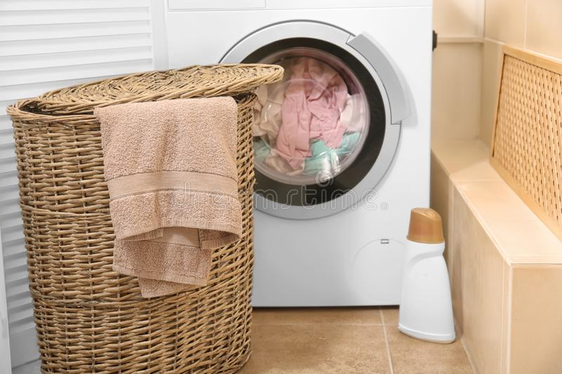 Wicker basket with laundry near washing machine. In bathroom stock images