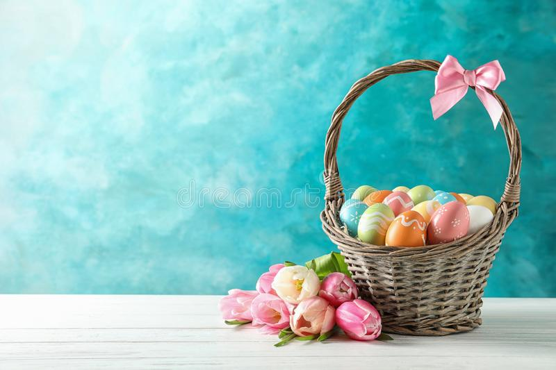 Wicker basket with painted Easter eggs and flowers on table against color background stock photography