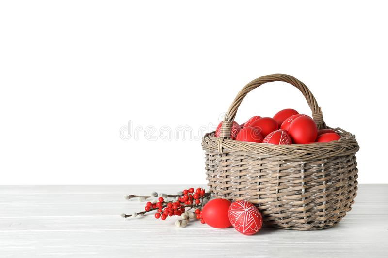 Wicker basket with painted red Easter eggs on table against white background royalty free stock photography