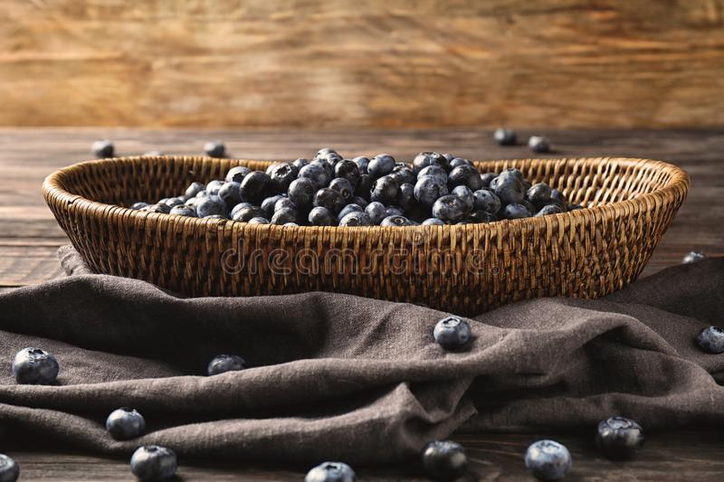 Wicker basket with ripe blueberries on table royalty free stock photo
