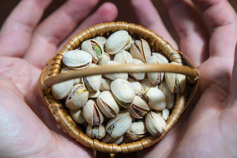 Wicker basket with salty, crunchy pistachio nuts between mans hands.  stock images