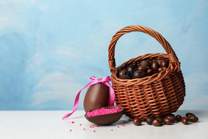 Wicker basket with sweet chocolate Easter eggs and dragee on table against color background royalty free stock photography