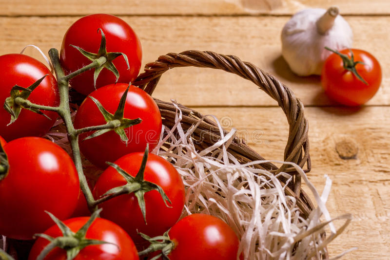 Wicker basket with tomatoes. Wicker basket nest with tomatoes and garlic on a wooden board royalty free stock photography