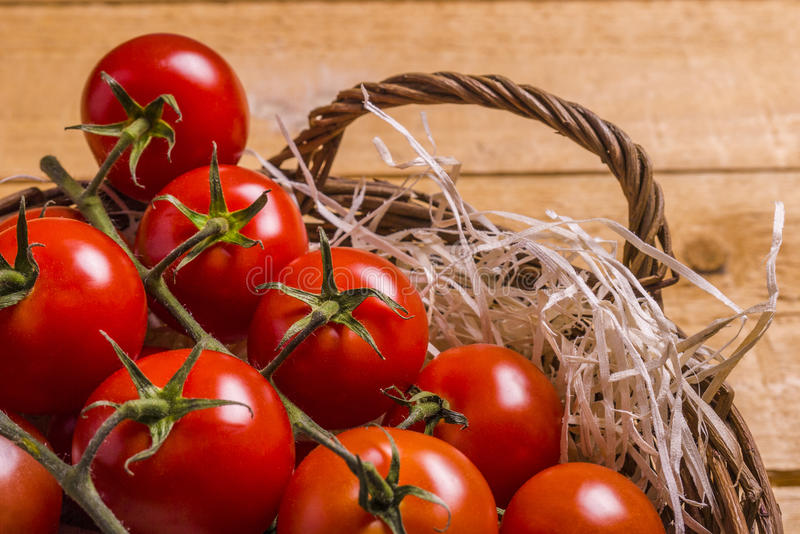 Wicker basket with tomatoes. Wicker basket nest with tomatoes on a wooden board stock photos