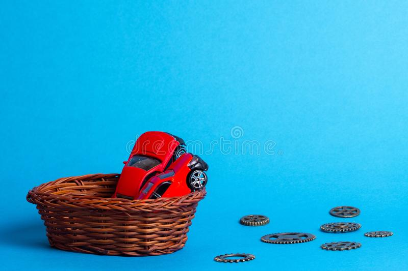 In a wicker basket of twigs are two red cars for children, next to the gears. Are made of metal stock photos