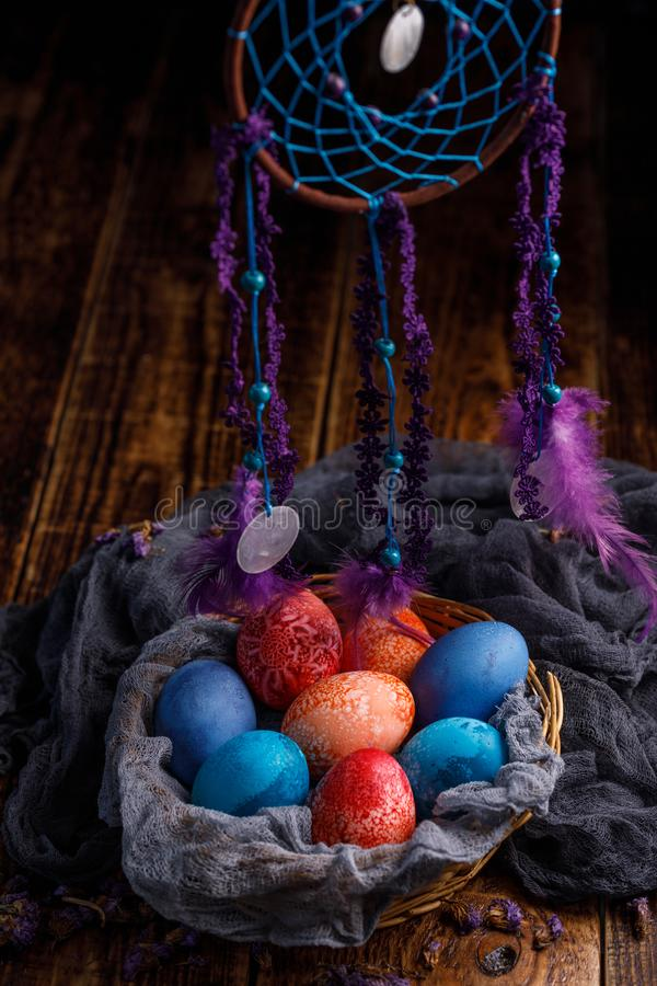A wicker basket with unusual colored Easter eggs and a series of hanging dreams catcher. stock photos