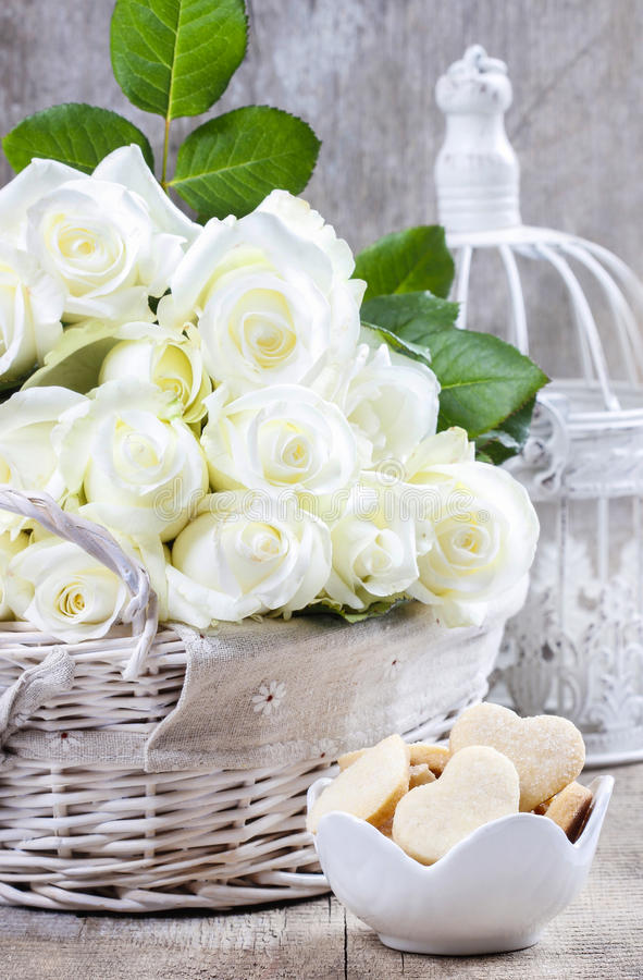 Wicker Basket Of White Roses And Bowl Of Cookies Stock Photo