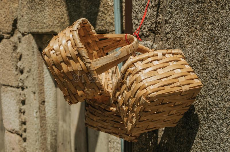 Wicker baskets tied together and hung on a wall of Monsanto. Wicker baskets tied together and hung in front of stone wall in a narrow alley, on a sunny day at royalty free stock photography