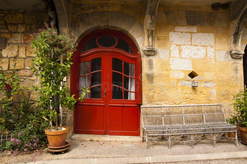 Wicker bench red door Saint-Cyprien Dordogne royalty free stock photography