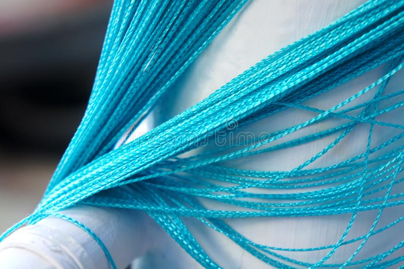 blue curtain of ropes Woven blue bright curtain of ropes hanging down royalty free stock photo