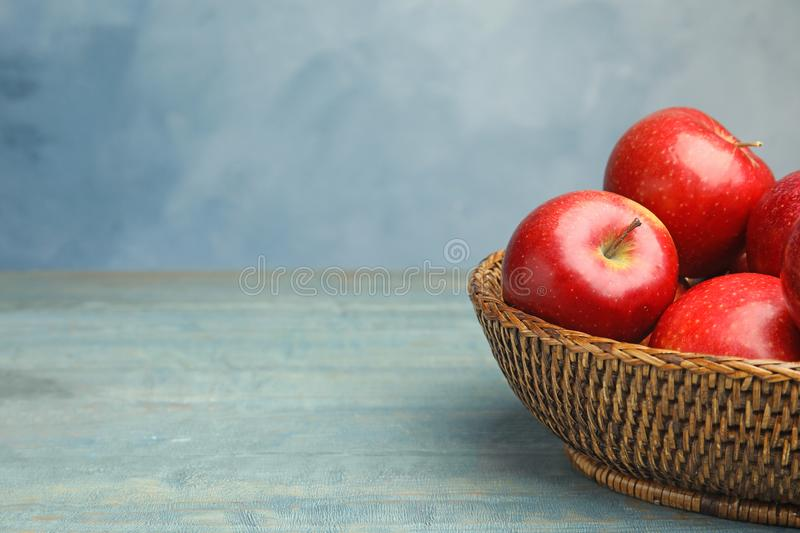 Wicker bowl with ripe juicy red on wooden table against blue background. Space for text. Wicker bowl with ripe juicy red apples on wooden table against blue royalty free stock photo