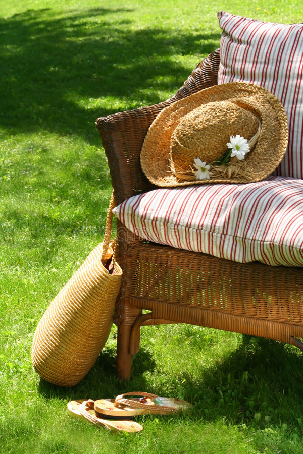 Wicker chair. Grass lawn with a wicker chair waiting for someone to relax on a hot summer's day royalty free stock photography