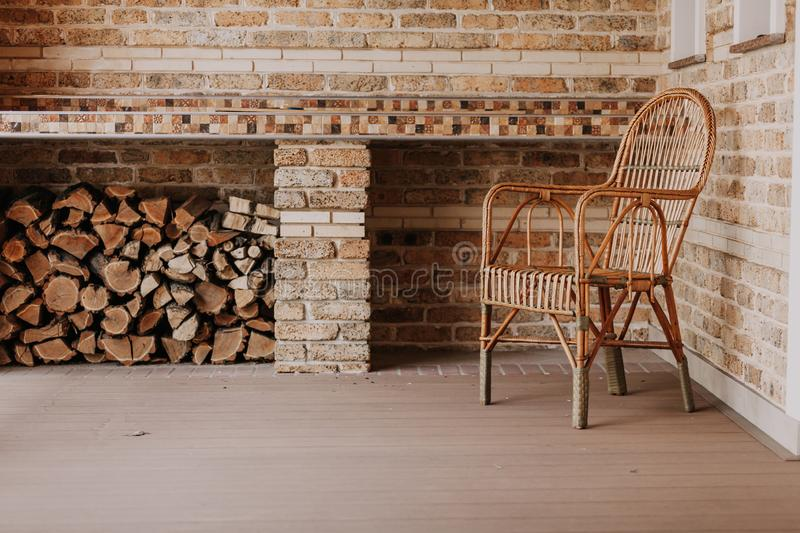 Wicker chair stands on autumn veranda. Autumn story light beautiful wicker chair from rattan stands on an empty veranda from behind lies a stack of punctured stock photography