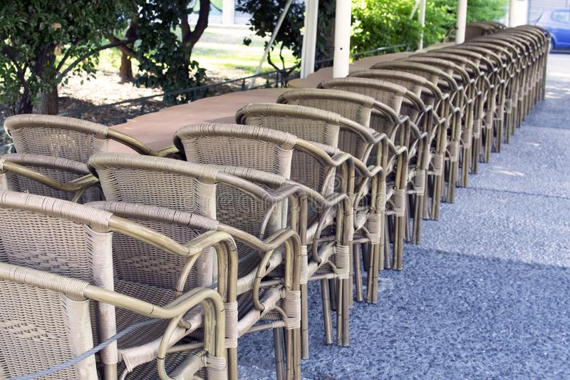 Wicker chairs stand in a row. The closure of the institution, storage of inventory. cafe, closing of the season. Furniture from the vine, rattan royalty free stock photo
