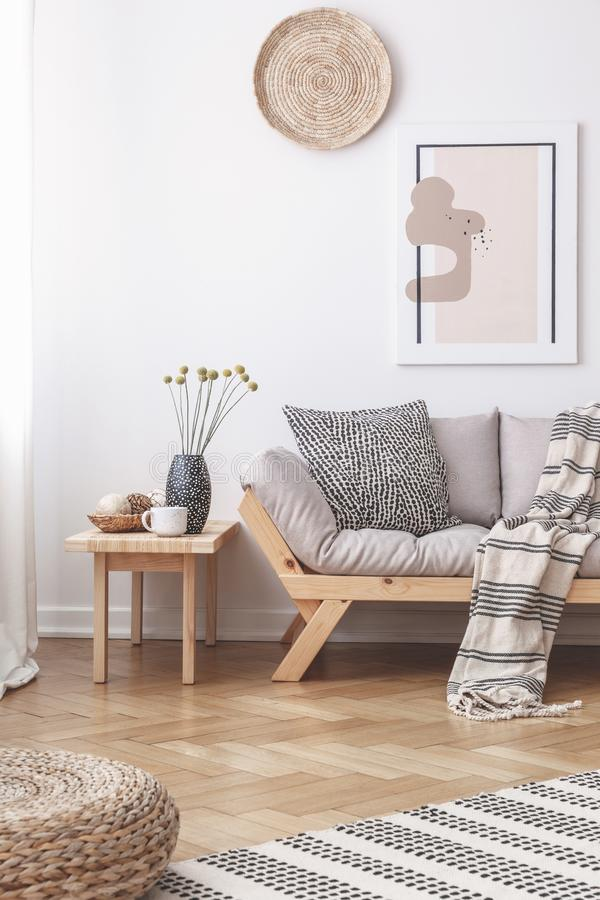 Wicker decorations and a painting on a white wall above a wooden sofa with cushions in a bright living room interior. Concept stock photography
