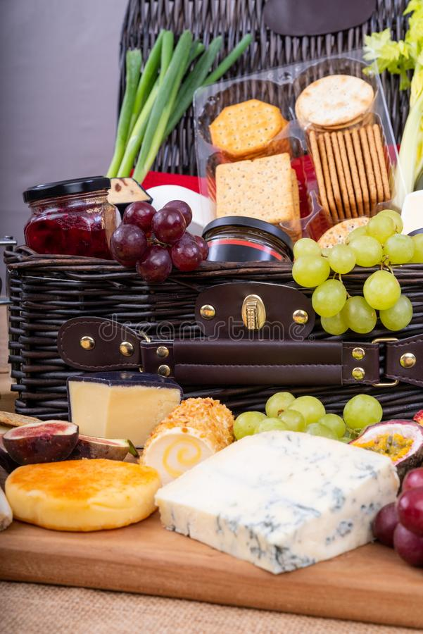 Chese and Cracker Hamper. Wicker Hamper with cheese pickles and crackers and a selection of fruit royalty free stock photography