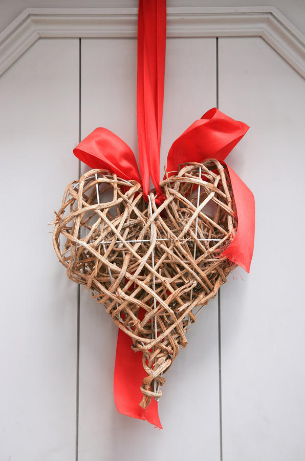 Wicker heart tied with a red ribbon to an old door stock photo