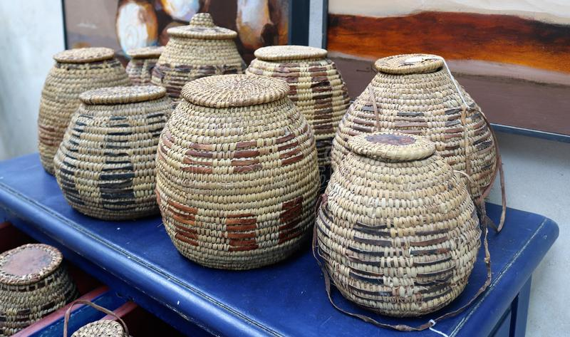 Wicker jugs for water. Traditional national wicker jugs for water on a blue wooden table royalty free stock photos