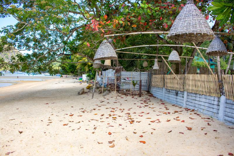 Wicker lamps hanging from trees on the beach, Philippines. Decoration of outdoor lanterns on seacoast. Tropical vacation. royalty free stock photos