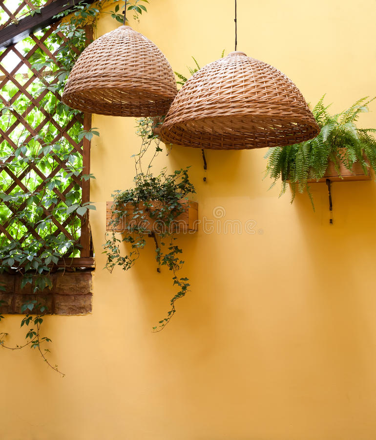 summer time garden building interior wicker lamp shade against a background of yellow wall