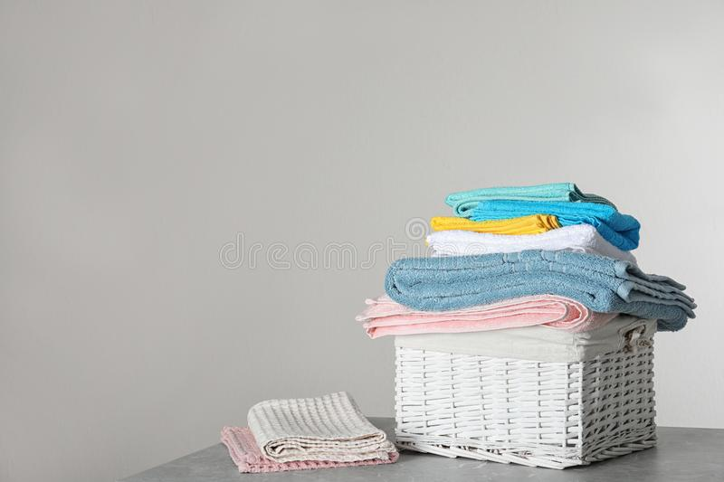 Wicker laundry basket with clean towels on table against light background. Space for text royalty free stock photos