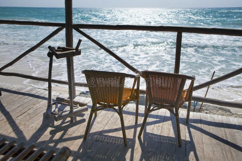 Wicker lounge chairs on the terrace overlooking the rippling Caribbean Sea. Cuba, Cayo Largo Island royalty free stock photos
