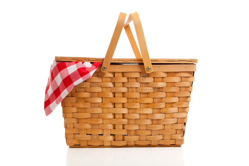 Wicker Picnic Basket with Gingham Cloth. A brown wicker picnic basket on a white background with gingham cloth royalty free stock images