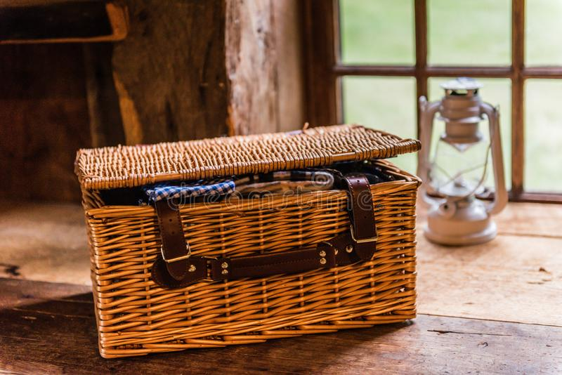 Wicker Picnic Basket On Shelf. A wicker picnic basket sits on wood bench, with blue ginham napkin peeking out stock photography