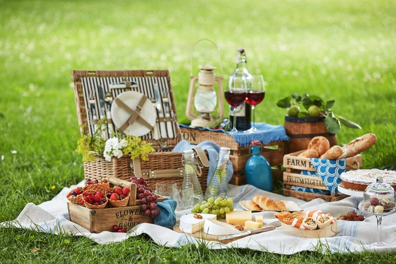 Wicker picnic hamper with assorted fresh food. Infused water and wine on a rug spread out on the green grass in a park stock photography