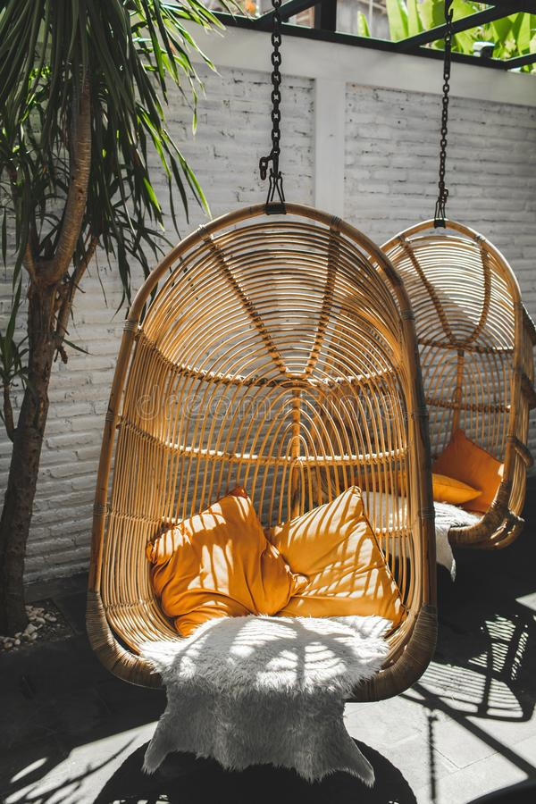 Wicker rattan hanging chair in loft hipster cafe. Wicker rattan hanging chair in loft cafe. Eco friendly furniture style and concept. Orange pillows and soft fur royalty free stock photography