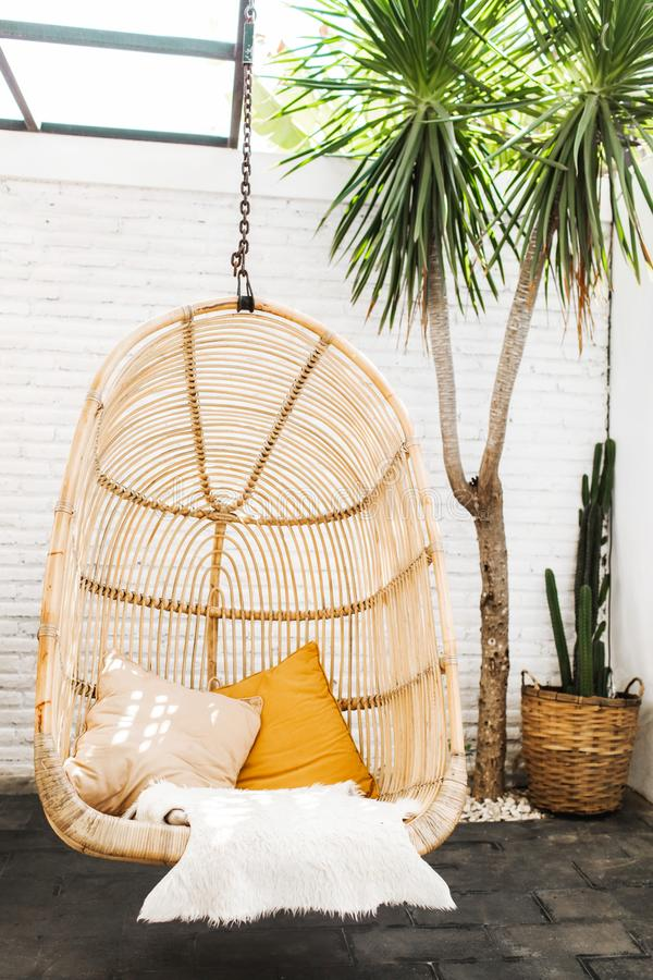 Wicker rattan hanging lounge chair in loft cafe. Wicker rattan hanging chair in loft cafe. Eco friendly furniture style and concept. Orange pillows and soft fur royalty free stock image