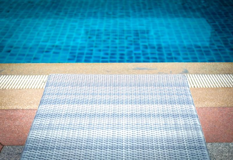 Wicker rattan pool sun bed deckchair at swimming pool royalty free stock images