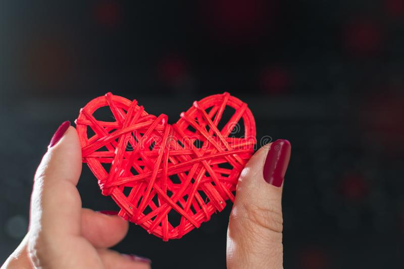 Wicker red heart in female hands on dark background royalty free stock image