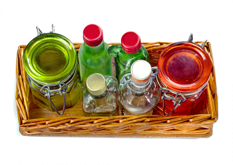 Wicker salver with empty glass jars and little glass bottle stock image