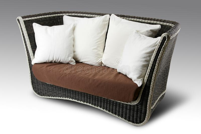 Wicker sofa with pillows royalty free stock photography