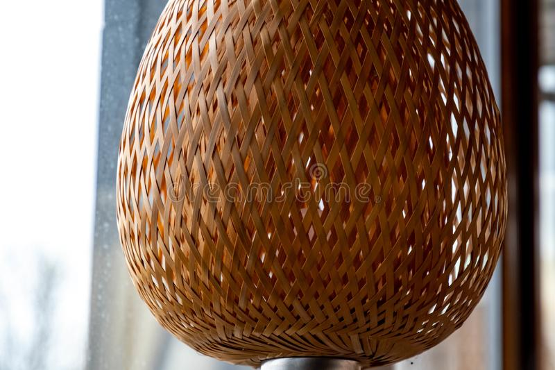 Wicker straw lampshade closeup. Natural crossed straw woven lattice texture with backlighting. Shaped lattice lamp. Light beige grid pattern. Geometric shapes stock illustration