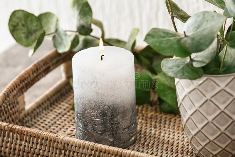 Wicker tray with burning candle and eucalyptus branches, closeup stock image