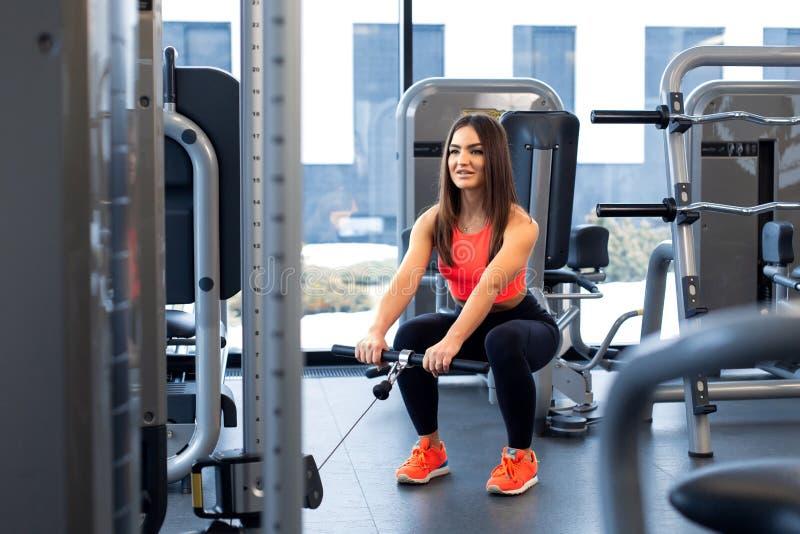 ?wiczenia w blokowym symulancie Bicepsa rozszerzenie Sportowy kobieta trening w gym obraz stock