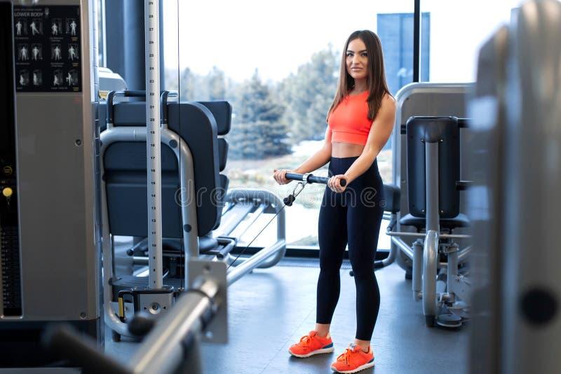 ?wiczenia w blokowym symulancie Bicepsa rozszerzenie Sportowy kobieta trening w gym obrazy royalty free