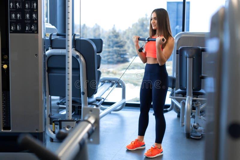 ?wiczenia w blokowym symulancie Bicepsa rozszerzenie Sportowy kobieta trening w gym zdjęcia royalty free