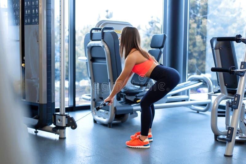 ?wiczenia w blokowym symulancie Bicepsa rozszerzenie Sportowy kobieta trening w gym zdjęcia stock