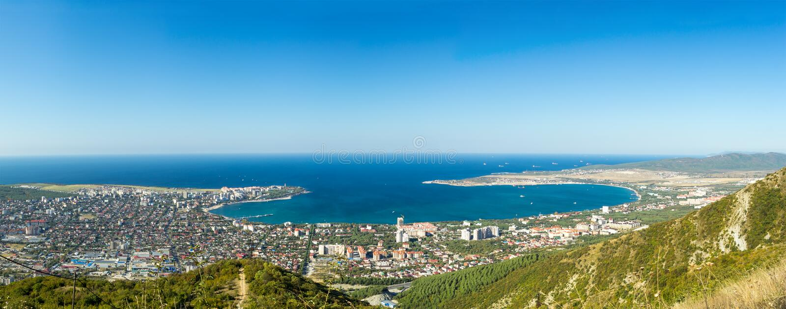 Wide aerial panorama of Gelendzhik resort city, Krasnodar region, Russia. View from hill of Caucasian mountains. Beautiful sea bay, buildings, houses, forest stock image