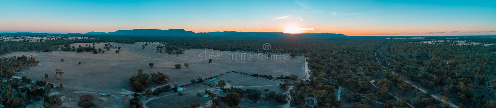 Panorama of Grampians mountains, farmland, and forest. Wide aerial panorama of Grampians mountains, farmland, and forest at sunset stock images