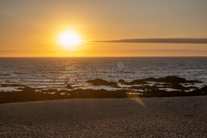 Wide angle beach sunset on a summer evening in Portugal. Beautiful soft gold light with lens flare stock photos
