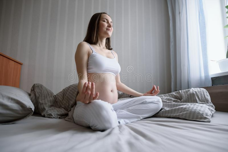 Wide angle bottom portrait of young pregnant woman relaxing and meditating in bed stock photos