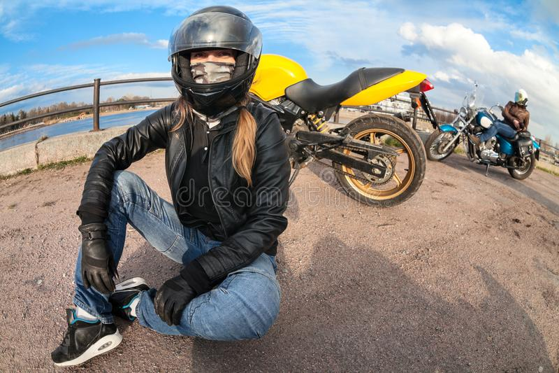 Wide angle of girl motorcycle rider sitting on earth next to bike and female biker with chopper on background royalty free stock images
